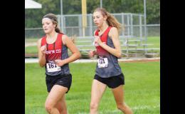 Seniors Emily Christensen (left) and Eme johnson run side by side in their last Ram Invitational cross country meet. Johnson and Christensen are two of Greene County's top five runners and usually reach the finish line within 15 seconds of each other.