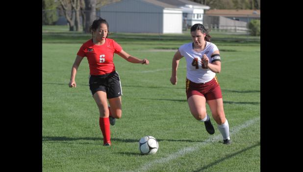 Greene County's Julia Saul (6) chases down PCM's Kimee Gallaher during a contest last spring in Grand Junction.  BRANDON HURLEY | JEFFERSON HERALD
