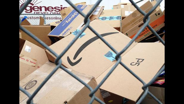 Amazon's smile-like arrow logo stands out on a cardboard box left for recycling outside Genesis Development in Jefferson.