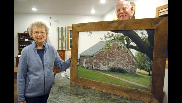 "Nancy (left) and Dean Rogers have put their vineyard and retreat center north of Scranton up for sale. ""It's been a good time, a good experience,"" Nancy says. They're pictured with a photo of the century-old barn they remodeled for use as a conference/meeting center and lodge. ANDREW McGINN 