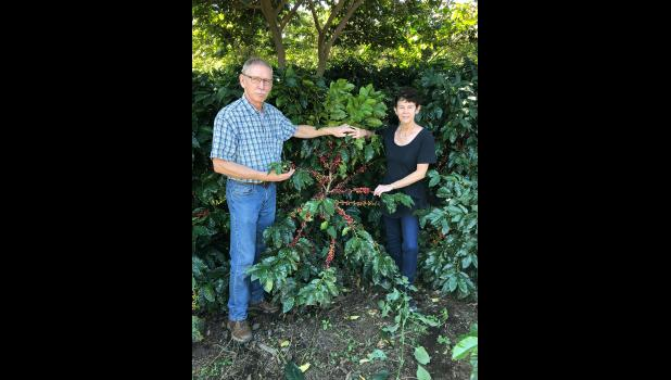The Rasmussens pose with ripened coffee cherries in El Salvador on the family coffee farm of Mario and Maria Mendoza, their son-in-law's parents.