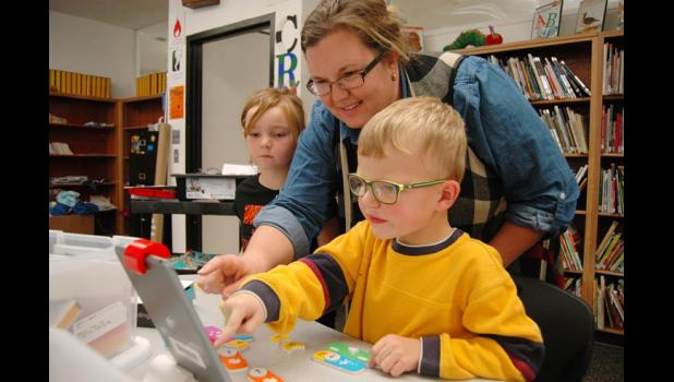 "Principal Annie Smith checks in with kindergartner Ean Hobbs at Paton-Churdan Community School as he plays a game that teaches a key aspect of computer programming. The school's ""maker space"" within its library has become a place where reading coexists with doing, with students encouraged to play around with everything from hot glue guns to iPads. HERALD FILE PHOTO"