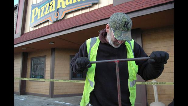 A city employee Wednesday works to turn the water off at Pizza Ranch following an overnight fire. ANDREW McGINN   JEFFERSON HERALD