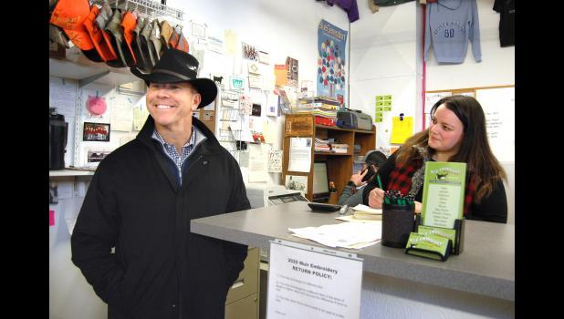 Bridget Johnson (right) glances up from a sale Jan. 21 at Muir Embroidery as her customer models his new hat to acquaintances. The customer was Democratic presidential candidate John Delaney, who was visiting businesses around the Square as part of a push in the final days before the Iowa Caucuses. He then walked a few doors down and bought a new refrigerator at John's Appliance. (Kidding.) ANDREW McGINN | JEFFERSON HERALD