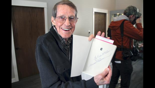 Evans McWilliam, of Paton, who was supporting author Marianne Williamson's White House bid, shows a book the candidate signed for him during a stop in Jefferson in early March. HERALD FILE PHOTO