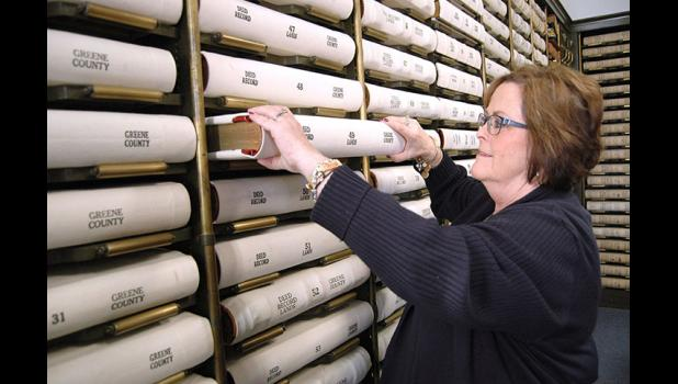 "County Recorder Marcia Tasler grabs a book containing deeds off the shelf in her office's vault. A $100,000 project would digitize some 91,000 land records dating back to 1854 and make them available online. ""It's the world we're in now,"" she says. ANDREW McGINN 