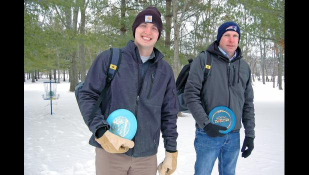 Daniel Rohner (left) and Steve Kohl hope to see the creation of an 18-hole, destination disc golf course at Daubendiek Park. The sport is scored like traditional golf, with golfers aiming their flying discs at a metal basket, er, hole like the one pictured at far left. Traditional golfers, however, are either giving up the game or dying by the thousands each year. Disc golf, which emerged from the laid-back hippie Frisbee culture of the '60s and '70s, is taking its place. ANDREW McGINN | JEFFERSON HERALD PH