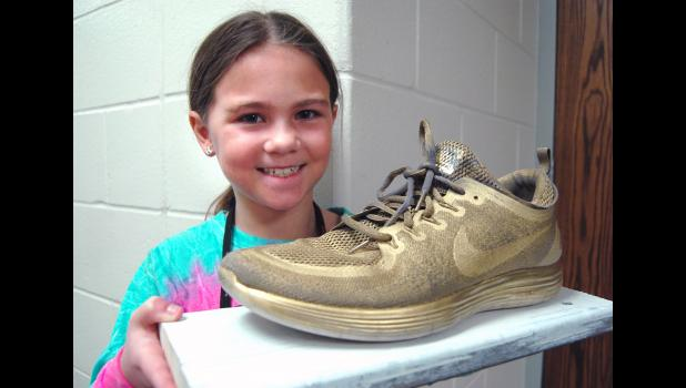 """Alaina Gettler, a third-grader at Greene County Elementary School, has walked nearly 40 miles at recess this school year, winning her class the right to host the """"Golden Shoe Award"""" created by PE teacher Sean Thompson as part of his new Mileage Club program. The real prize, however, are little plastic tokens shaped like feet that incentivize physical activity. ANDREW McGINN 