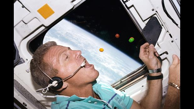 Commander Loren Shriver, a Paton native, is pictured in 1992 pursuing several floating M&M's on the aft flight deck of space shuttle Atlantis. Outside the window, the cloud-covered surface of the Earth is visible.