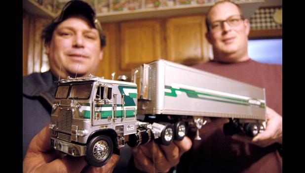 Brothers Robert (left) and Wayne Kafer hold up the diecast model of their late dad's truck that will hold his ashes. Bill Kafer, who died on Jan. 27, spent a lifetime in and around trucks, but his favorite was the silver, 1978 Freightliner cab-over with green and white stripes. ANDREW McGINN | JEFFERSON HERALD
