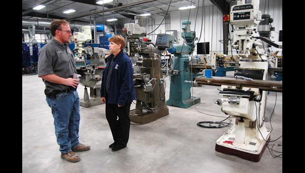 Colleen Bartlett (right), career academy specialist at the North Central Career Academy in Eagle Grove, speaks to Iowa Central welding instructor Branden Otto amid the lathes and mills of the academy's computer-integrated fabrication area. ANDREW McGINN | JEFFERSON HERALD