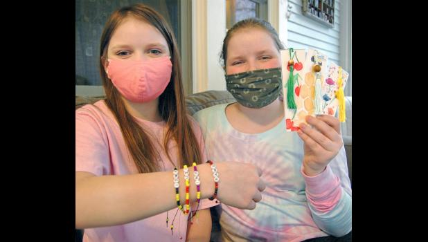 Sisters Amelia (left) and Adi Gallagher have been remote learners this school year because of the pandemic. They also started making bracelets and bookmarks while in isolation, donating $500 in profits to PAWS. ANDREW McGINN | JEFFERSON HERALD