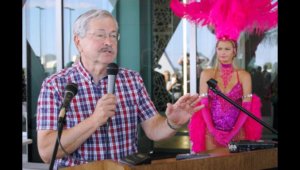 Then-Gov. Terry Branstad does his best not to be upstaged by a showgirl outside Wild Rose Jefferson in 2015 during a three-day grand opening celebration for the $40 million casino-events center. HERALD FILE PHOTOS