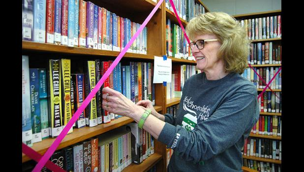 "Shari Minnehan, director of the Churdan Public Library, overlooks books that will need to be moved to make way for a $350,000 expansion and renovation of the library. The library raised enough money for the project ""one spaghetti supper at a time,"" Minnehan says. ANDREW McGINN 