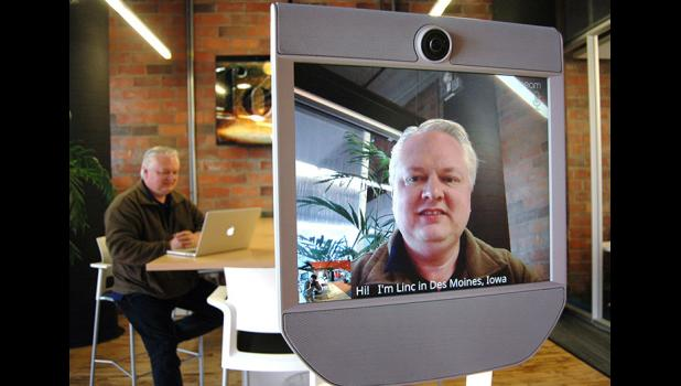 "Pillar Technology's Linc Kroeger (left, as well as right) shows off the mobile ""telepresence device"" that will enable software developers and technology consultants in Jefferson to interact flawlessly with co-workers as far away as Silicon Valley. Pillar will open an office in Jefferson in spring 2019, the first high-tech company to take a gamble on rural Iowa. ANDREW McGINN 