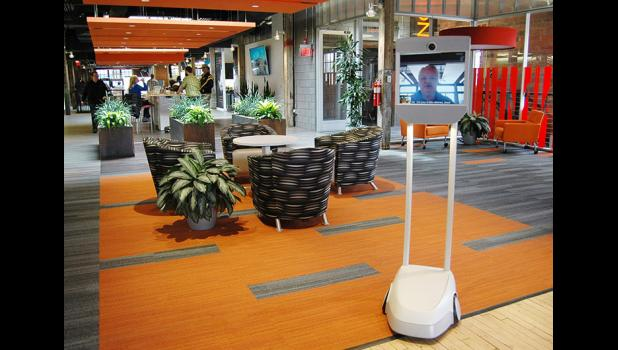 "Visitors from afar get to roam Pillar's Des Moines office via a Beam, the wheeled ""telepresence device."""