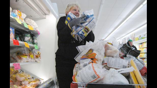 Tammy Smith grabs as much meat as she can Saturday morning at the Jefferson Fareway as part of a two-minute shopping spree she won from Our Iowa magazine.