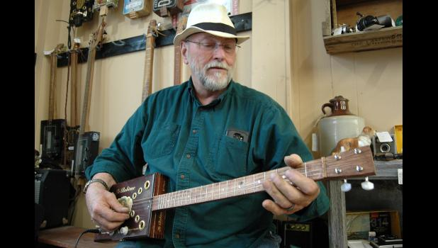 """What kills me is they ask, 'Do they work?' "" says Ken Bose, playing his latest cigar box guitar. Bose's shop on the Square, Skeeter Creek Fabricators, is home to an eclectic mix of antiques and art, but his handmade creations are everywhere you turn. ANDREW McGINN 