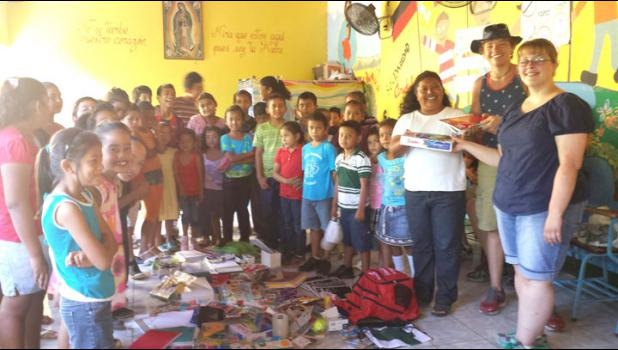 Greene County High School seniors Karter Ruzicka and Kate Beyerink give donated school supplies to a rural school in Granada, Nicaragua.