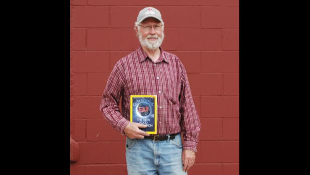 Churdan farmer George Naylor holds the issue of National Geographic that he's featured in.