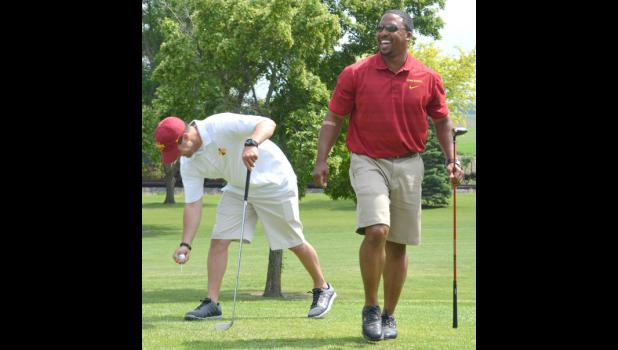 Maurice Linguist, secondary coach for the Iowa State football program, laughs Friday after trying his hand at golf while another coach tees off at the golf tournament hosted by Cecil Rueter of Grand Junction.