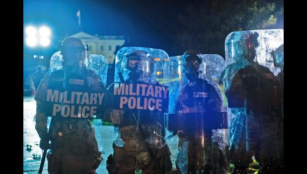 "Riot control troops stand in position May 30 near the White House as demonstrators protest systemic racism following the killing in Minneapolis of George Floyd, a black man, by a white police officer. Jefferson native Nicole Peckumn is close to the action as interim deputy communications director for Washington, D.C., Mayor Muriel Bowser, who has expressed concern about President Donald Trump's response to the demonstrations in the city, including the use of unidentified federal personnel operating ""outside"