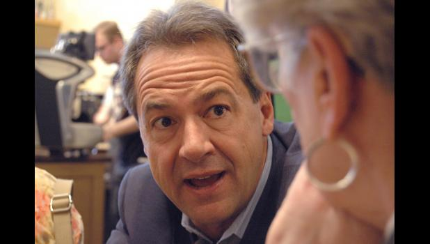 Montana Gov. Steve Bullock crouches down Monday at Greene Bean Coffee to talk with Jean Tucker, of Jefferson, during a campaign stop. ANDREW McGINN | JEFFERSON HERALD