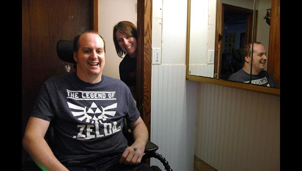 """His sense of humor was never lost."" Lacy Follett-Brubaker (right) peers around the corner Friday of the bathroom she gutted and modified with the help of family and friends to accommodate her husband's new wheelchair. Adam Brubaker, 39, suffered a herniated disk in his neck Dec. 28 that left him paralyzed. ANDREW McGINN 