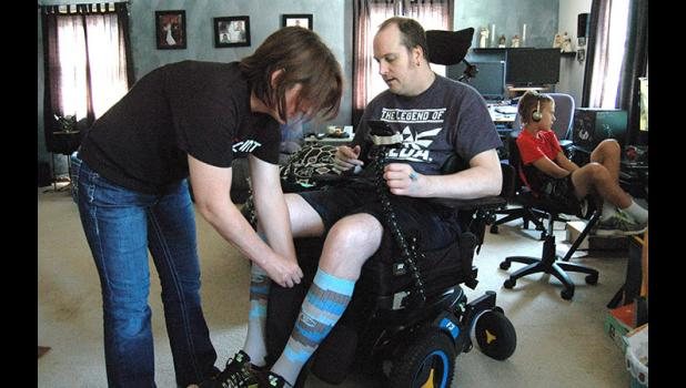 A new normal: Lacy Follett-Brubaker readjusts the urine drainage bag on her husband's wheelchair as their 9-year-old son, Jacob, watches a show on the computer.