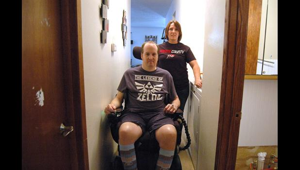 "Adam Brubaker rolls down his bedroom hallway Friday, his first full day back home after six and a half months of therapy in Nebraska. ""I'm prepared for him to tear up my house with his wheelchair,"" says wife Lacy Follett-Brubaker."