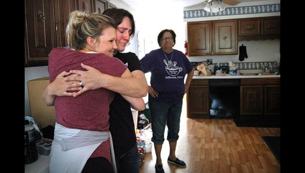 "Lacy Follett-Brubaker (center) embraces the nurse from Omaha who brought her husband, Adam, home. Phyllis Bunkers soon arrived with a welcome home bag of Bunkers Dunkers doughnuts containing Adam's favorite: fried cinnamon with maple frosting. ""This is a special deal when you have your doughnuts delivered to you,"" Lacy said. ANDREW McGINN 