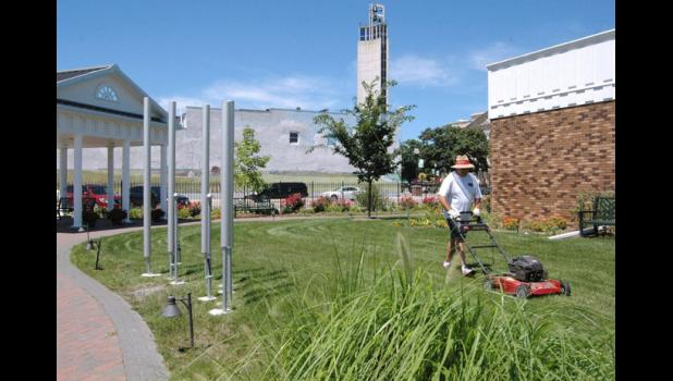 Thomas Jefferson Gardens board member John Turpin mows Monday near the site's new playable contrabass chimes (left). A new grant will allow the board to finish remodeling the building on site to serve as a Greene County welcome center and a Thomas Jefferson interpretive center. ANDREW McGINN | JEFFERSON HERALD