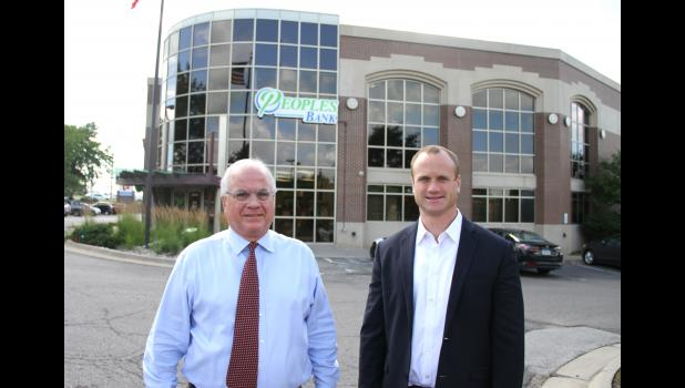 Greene County Development Corp. member John P. Rigler III (right) stands with his dad, John P. Rigler II, outside the Peoples Bank branch in Clive. Rigler III is president of the bank, which has operations in Jefferson, Scranton, Grand Junction and Rippey.