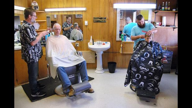 Double the action: Jefferson barber Chuck Bradshaw II (left) recently welcomed his son, Charlie (right), into his downtown barbering business. The addition of a second chair at Chuck's Barber Shop recalls the golden age of local barbershops, when there were enough heads in town to support five competing barbershops, each with two barbers. ANDREW McGINN | JEFFERSON HERALD PHOTOS
