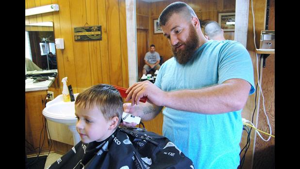 Donavon Wetzel, 4, of Linden, gets his hair cut by Charlie Bradshaw. Bradshaw is the third generation of his family to wield clippers.