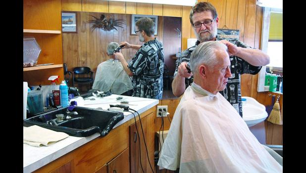 "Dennis Kemble sits for a recent haircut at the Jefferson barbershop owned by Chuck Bradshaw II. Bradshaw followed his father into barbering: ""He always said people are always going to get their hair cut no matter what."" ANDREW McGINN 