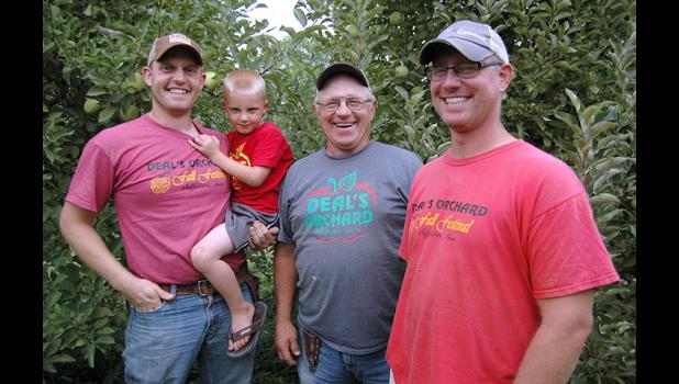 Three generations of Deals: Jerald Deal (center) has been joined in recent years in his apple orchard by sons Benji (right) and Chris (left), holding his son Aidan, 4. For 100 years, the Deal family has been growing apples just west of Jefferson. Deal's Orchard plays host to thousands each fall. ANDREW McGINN | JEFFERSON HERALD