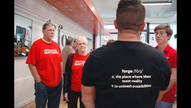 "Clad in their ""Jefferson Matters"" shirts, Jefferson residents Roger (left) and Jan Aegerter take a tour Saturday of the Forge with an Accenture software artisan. ANDREW McGINN 
