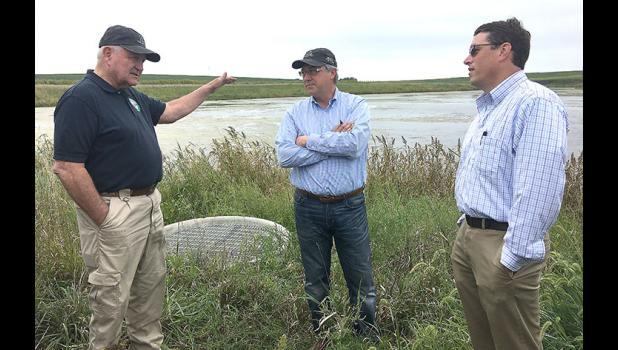 U.S. Secretary of Agriculture Sonny Perdue (left) speaks with Congressman David Young (center) and John Rutledge, Lake Panorama Association general manager, at a wetland visited recently by Perdue and others that helps protect Helen's Cove.