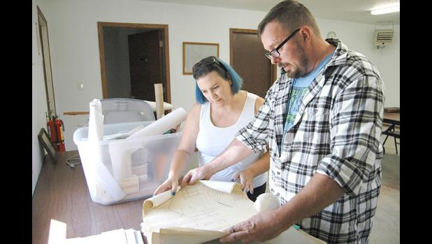 "Mayor Mandy Sims (left) and husband Tony, a Dana city councilman, look over old building plans at Dana City Hall. The two 40-somethings admit that saving Dana is an uphill battle, and that not everyone shares their vision. ""Truth be told,"" Tony says, ""I'm pretty sure everyone in this town hates us."" ANDREW McGINN 