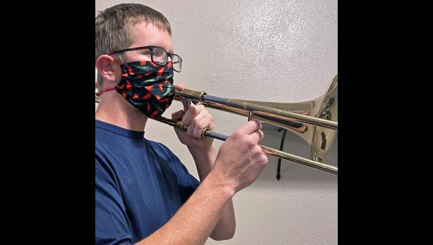Greene County High School band teacher Wes Anderson demonstrates how it's possible to play a trombone while wearing a mask. In a band setting, the trombone's bell would also be masked. One recent study recommended that trombones be given nine feet of distance to mitigate spread of coronavirus, instead of the usual six feet, with the use of puppy pads for spit valves.