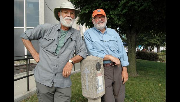 Jefferson natives Rich Stream (left) and Tim Donovan are walking across Iowa along the historic Lincoln Highway, an expedition of nearly 400 miles. They passed through their hometown last week and posed next to one of the surviving concrete markers placed along the entire Lincoln Highway by Boy Scout troops nationwide in 1928. ANDREW McGINN | JEFFERSON HERALD
