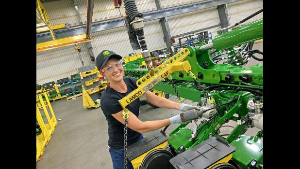Lt. Claire Wilson tries her hand out on the production floor at John Deere Paton. The naval officer is spending her final days of active-duty service in Paton through the Department of Defense SkillBridge program.