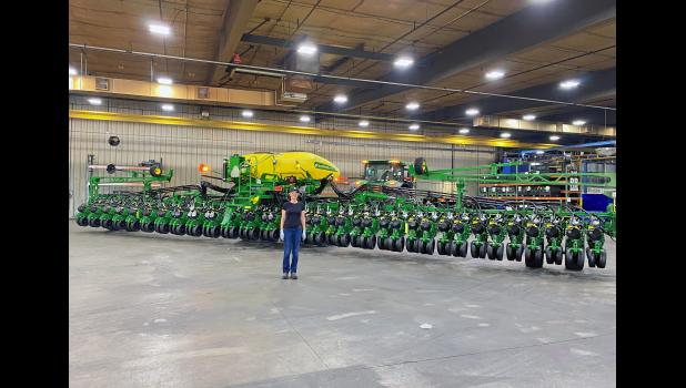 U.S. Navy Lt. Claire Wilson gets her photo taken at John Deere Paton in front of what can only be described as a Nimitz-class planter: the DB60, a 36-row planter.