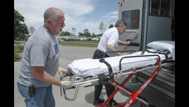 Dennis Morlan and EMT Matthew Roberts (left), of Greene County EMS, unload a stretcher at the scene of a two-vehicle crash at Vine and Washington streets in Jefferson. With Morlan hoping to retire, how to continue the ambulance service has emerged as the most pressing issue in the race for county supervisor. HERALD FILE PHOTO