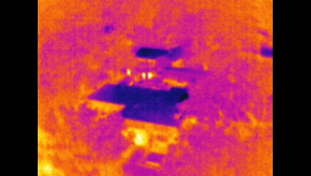 The same image, in thermal mode, identifies three heat signatures from the officers in yellowish white.
