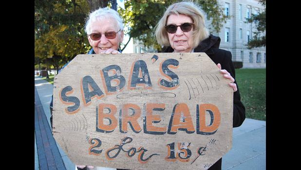 Jerry Kelley (left) recently unearthed an antique sign from the days of Saba Saba's bakery and gave it to Pauline Borst (right), Saba's adopted daughter. Saba ran a beloved bakery in Jefferson from 1925 to 1976. ANDREW McGINN | JEFFERSON HERALD
