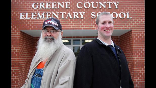 "Top Dogs: Dennis Hendricks (left) and the Rev. Devin Wolters hope to bring the national Watch D.O.G.S. program to Greene County Schools. The volunteer program puts positive male role models in the schools who also act as extra eyes and ears for teachers and principals. ""Women are already in there,"" Wolters says. ""It's time that men step up."" ANDREW McGINN 