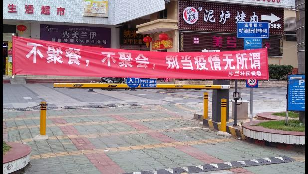 """Miller resides part-time in Shenzhen, China, a city of about 20 million. """"They took it seriously from Day 1,"""" he says of the Chinese response to COVID-19. This banner, pictured in March, warns: """"Don't eat together, don't meet up, don't be indifferent to the epidemic."""""""