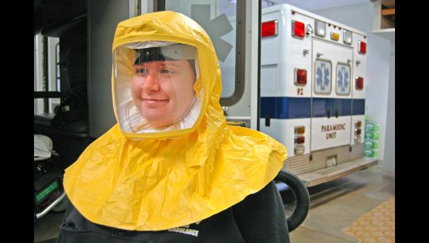 """Allie Powell, a Greene County Ambulance EMT, dons one of the powered, air-purifying respirators, or PAPRs, available to local medics amid the pandemic. """"Any call,"""" says Michele Madsen, Greene County Ambulance director, """"could become exactly that: a Covid call."""" ANDREW McGINN 